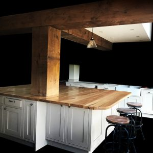 Large rural yet modern and contemporary kitchen with large feature oak kitchen island top matching rustic styled structural beams