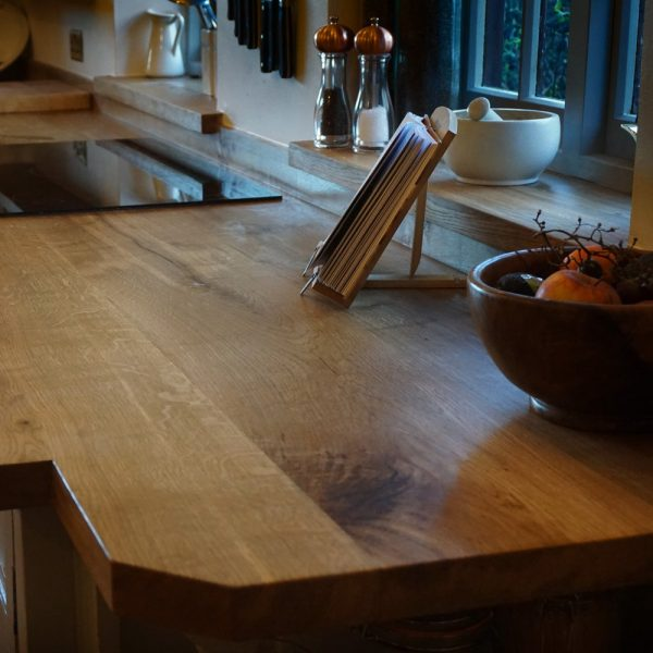 Custom cut earthy English oak worktop showing unique earthy grains in warming radiant rustic styled kitchen