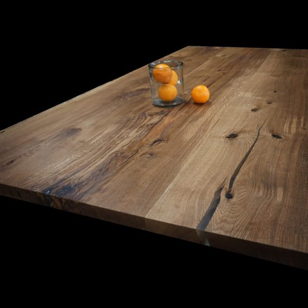 Beautiful resin infilled natural imperfections on oak dining table top with beautiful unique grain showing