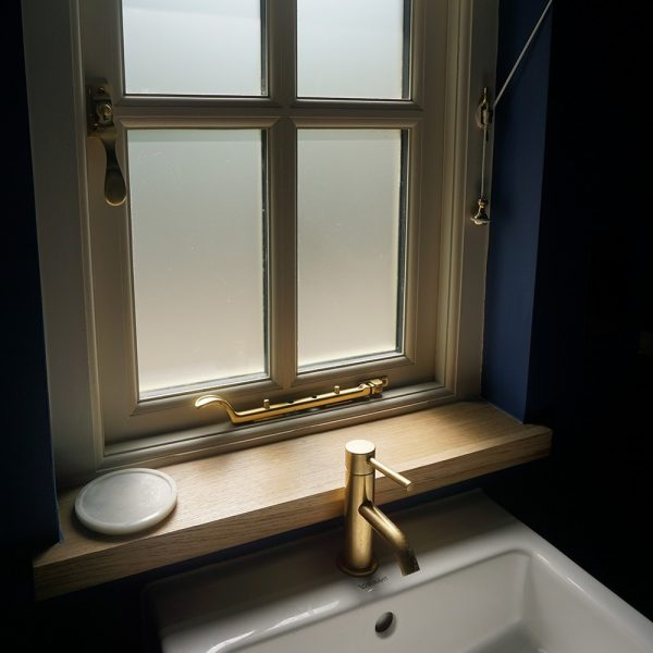 Beautiful bespoke earthy hand-crafted oak window sill in modern cottage style bathroom