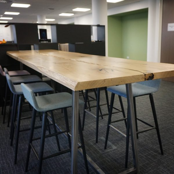 Beautiful earthy oak table with mixed edge high tables in modern contemporary office space