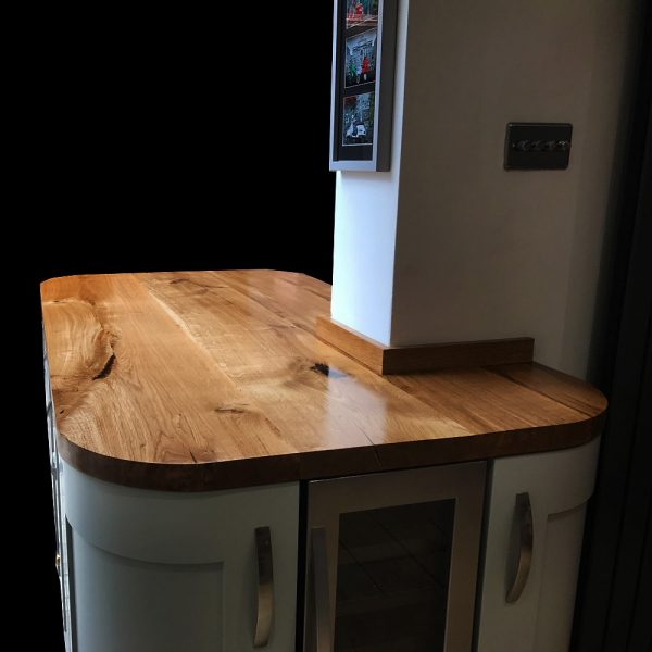 Beautiful solid wooden rounded corner oak kitchen island with straight edging on modern contemporary white units