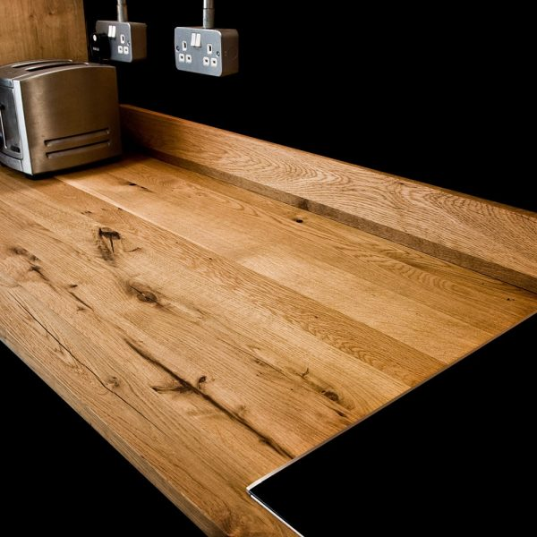 Custom crafted resin infused rustic oak worktop with matching upstands in modern contemporary kitchen