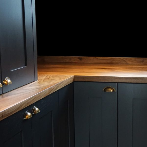 Unique earthy wild walnut worktops with matching upstands in modern contemporary styled kitchen with navy kitchen cupboards