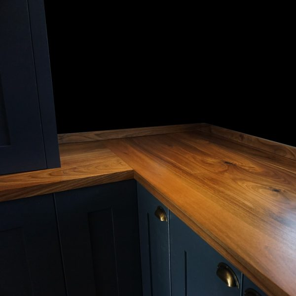 Bespoke wild walnut worktops in L shape with matching upstands on modern contemporary navy coloured units