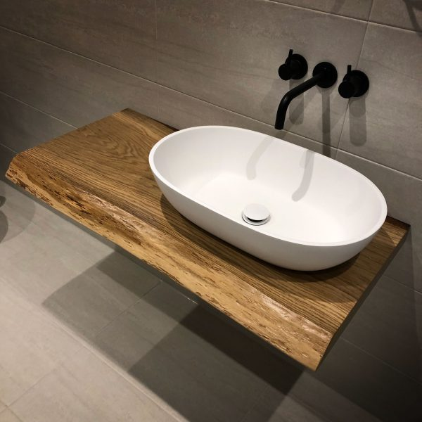 Beautiful bespoke hand-crafted oak bathroom sink top with live edging in modern contemporary bathroom