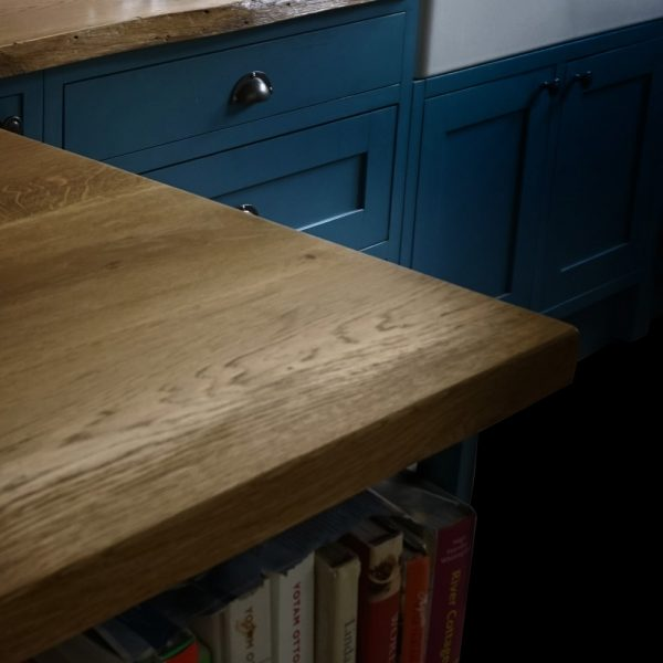 Beautiful rustic live edged oak worktops on modern contemporary navy cupboard units