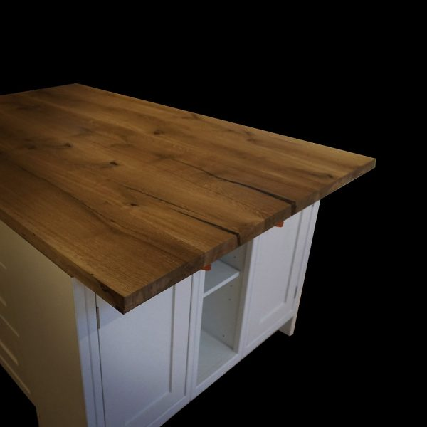 Beautiful stained rich earthy oak kitchen island top with unique resin infused natural cracks on white units