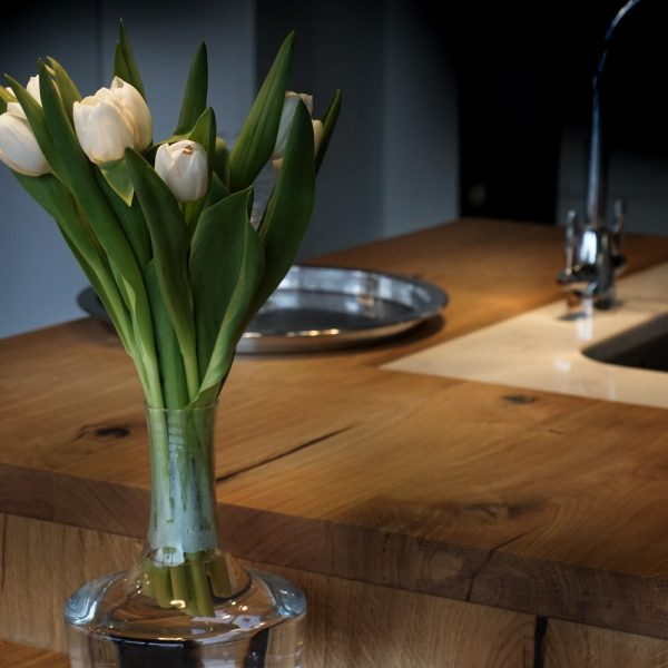 Beautiful hand-crafted wooden worktops with unique earthy grain detail showing in modern contemporary kitchen