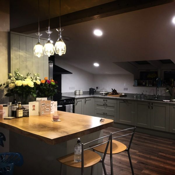 Beautiful modern contemporary styled kitchen with earthy live edged oak kitchen island top with additional curved edging