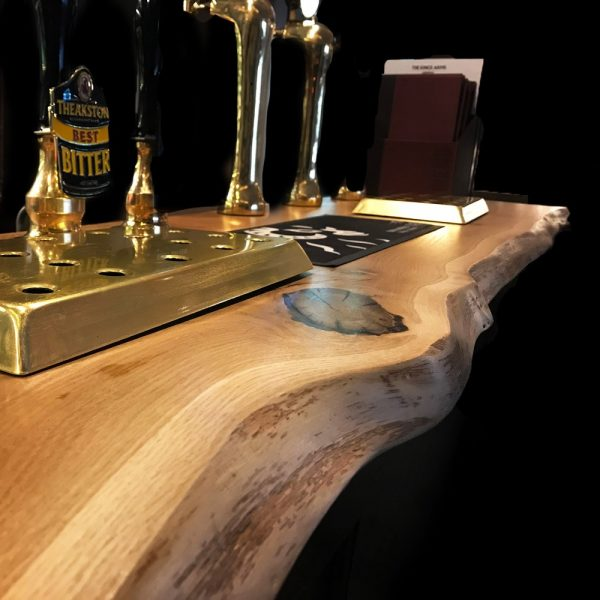 Stunning waney edged oak bar top with custom cut outs for pumps in bar/ pub