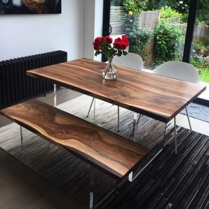 Beautiful modern contemporary styled dining room with earthy contemporary wild walnut table with acrylics legs and matching bench