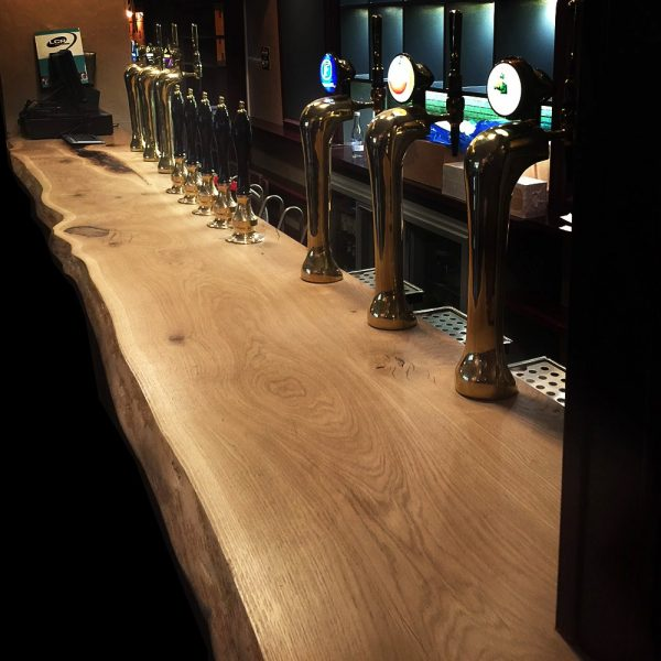 Rural rustic waney edged style bar top with custom cut outs in modern contemporary pub/ bar
