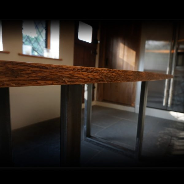 Beautiful live edging detail of earthy oak table with u shaped steel legs in modern contemporary kitchen