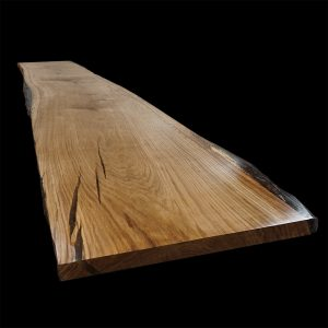 Beautiful live waney edged oak table top showing earthy grain and resin infilled cracks and striations