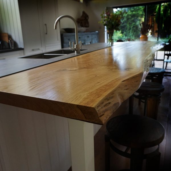 Beautiful bespoke soldi wooden bar tops with rustic oak waney edging and resin infill