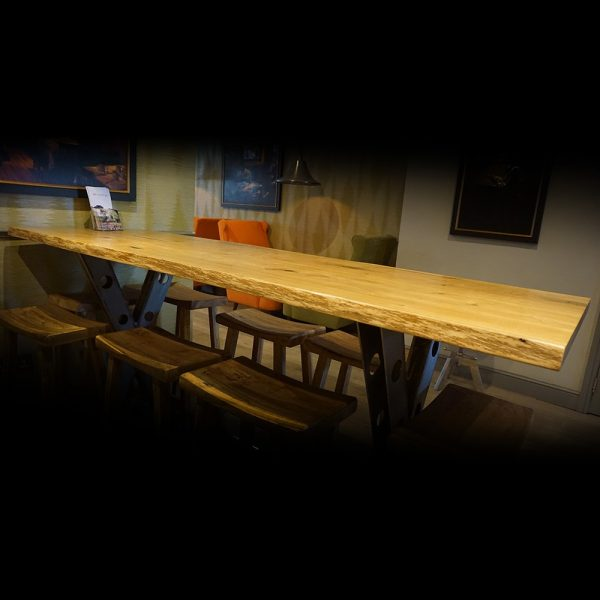 Bespoke rustic oak desk top in rural rustic hotel lobby with waney live edges and industrial styled steel legs