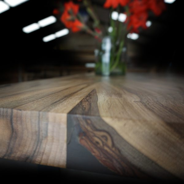 Beautiful edging detail showing bark preservation and resin infused natural imperfections on wild walnut desk top