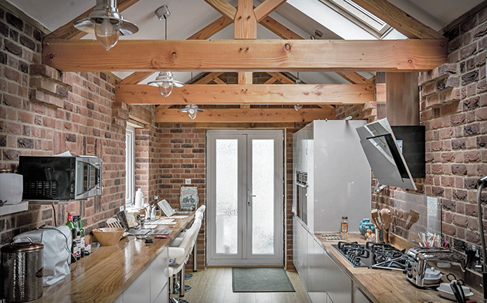 Beautiful oak worktops in modern bricked kitchen with rustic styled beams