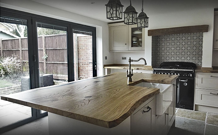 Waney Edged rustic oak kitchen island with matching worktops and upstands in modern light airy kitchen
