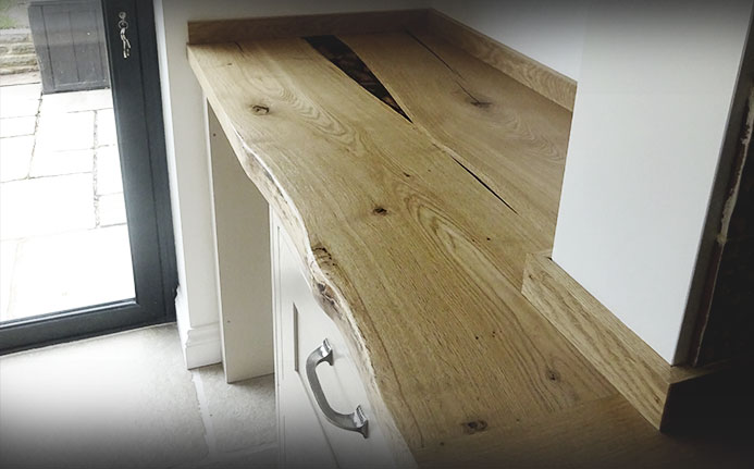 Beautiful unique solid oak waney edged worktops with matching upstands in light airy kitchen