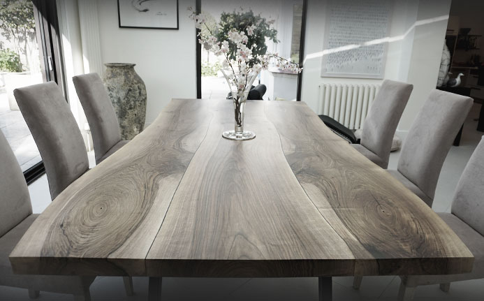 Beautiful wild walnut earthy live edged dining table with trapezium legs in modern dining room
