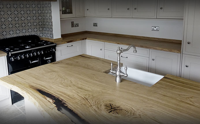 Beautiful resin infilled luxury range waney edged oak kitchen island with matching worktops in light airy modern kitchen